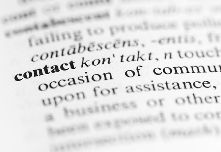 Close up of the word  contact  and its definition in the dictionary