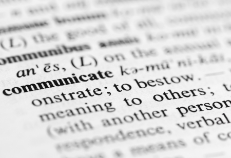 Close up of the word  communicate  and its definition in the dictionary