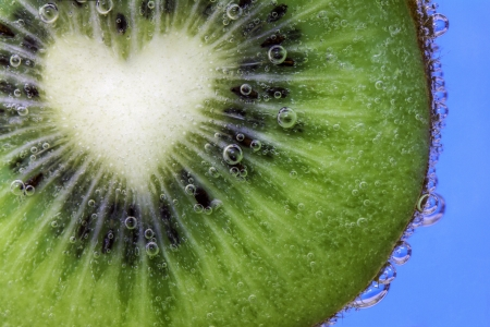 Closeup of a heart shaped kiwi slice covered in water bubbles photo
