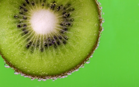 Closeup of a kiwi slice covered in water bubbles against a green background photo