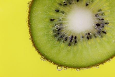 Closeup of a kiwi slice covered in water bubbles against a yellow background