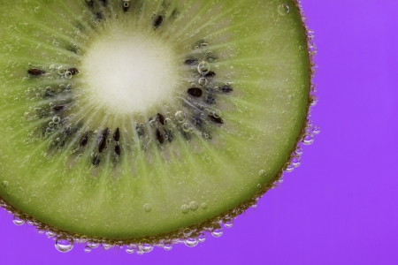 Closeup of a kiwi slice covered in water bubbles against a purple background