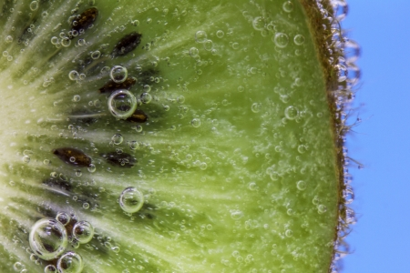 Closeup of a kiwi slice covered in water bubbles against an aqua blue background