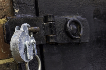 A close up of a strong looking silver padlock on a black metal door
