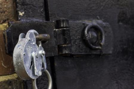 puerta de metal: Un primer plano de un fuerte candado de plata mirando a una puerta de metal negro