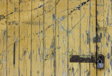 lockup: A rustic and weathered orange padlocked door Stock Photo