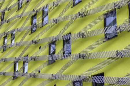 Striking and unusual looking modern yellow office building with metal mesh lattice pattern Zdjęcie Seryjne