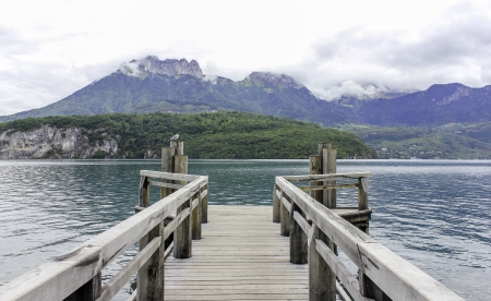 A beautiful view down a pontoon on an aqua green lake with dramatic mountains behind