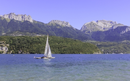 A sailing boat on a stunning blue lake with a fabulous mountainous backdrop