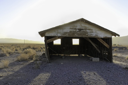 rickety: A deserted old rickety hut or shed leaning to one side in the desert with the setting sun creating a silhouette behind