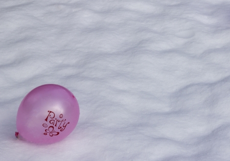 A bright pink purple balloon with  Party  written on it lying in the snow photo