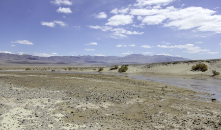 An image of a nearly dried out river bed in the desert with mountains in the distance