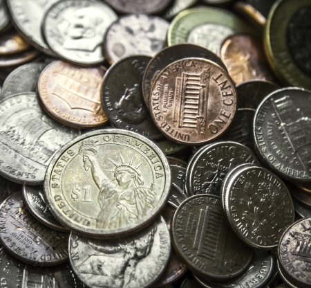 Close up on a pile of American coins US money with main focus on one Dollar coin