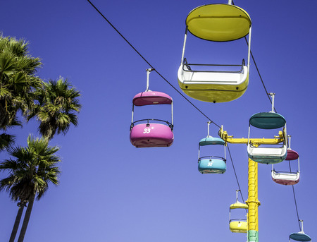 Brightly colored striking cable cars and palm tree set against a deep blue sky Publikacyjne
