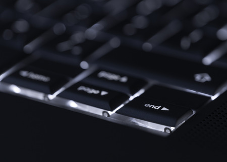 standout: Closeup of backlit computer laptop keyboard selective focus on end key ideal for technology night hacker standout