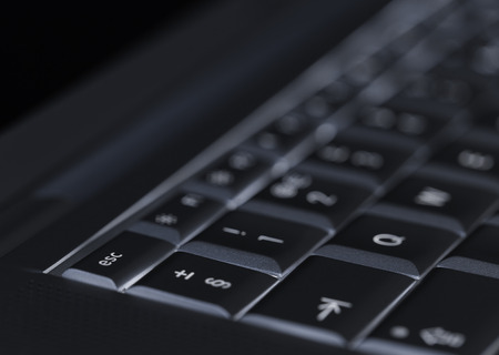 Closeup of backlit computer laptop keyboard selective focus on escape key ideal for technology night hacker standout