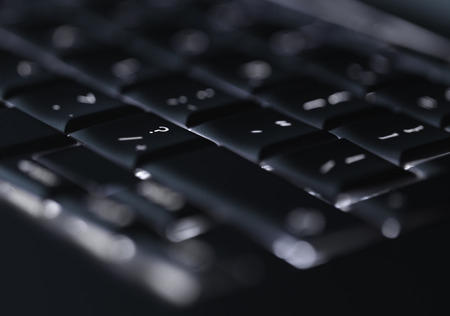 cyber crime: Closeup of backlit computer laptop keyboard selective focus on question mark key ideal for technology support night hacker standout Stock Photo