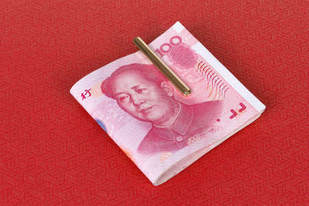 stack of yuan notes on red background