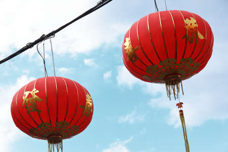 two red chinese lanterns against cloudy sky