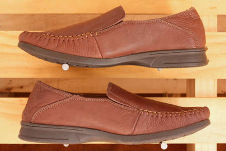 men brown genuine leather shoes on wood background photo