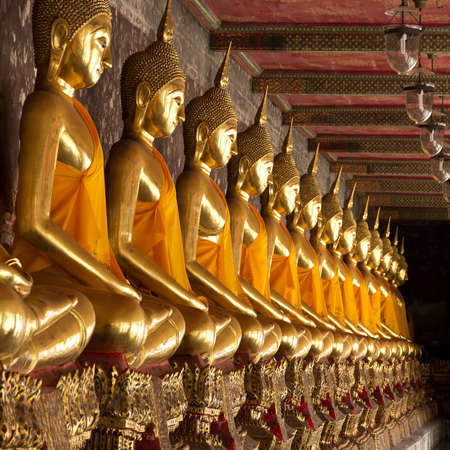 golden buddhas lined up along the wall of buddhist temple Stock Photo
