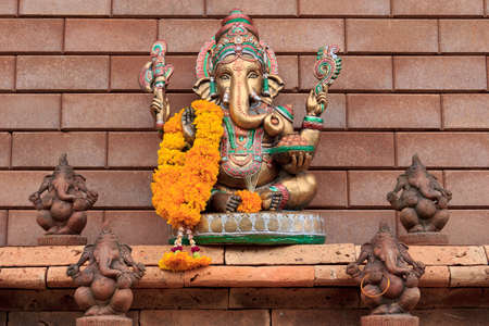 hindu god: golden ganesha on brick wall