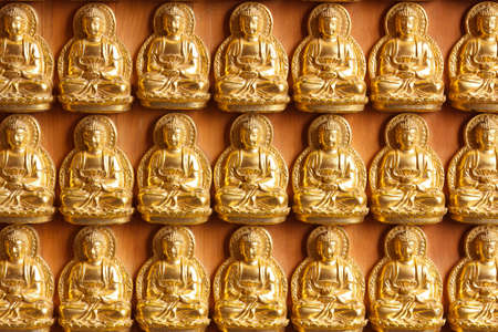 lined up: golden buddhas lined up along the wall of chinese temple Stock Photo