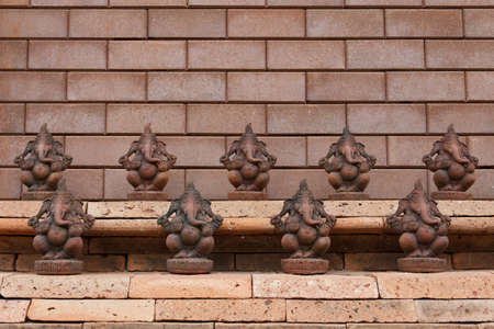 indian culture: little clay ganesha lined up along the brick wall Stock Photo