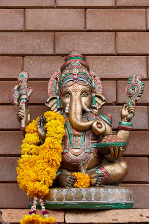 golden ganesha on brick wall photo
