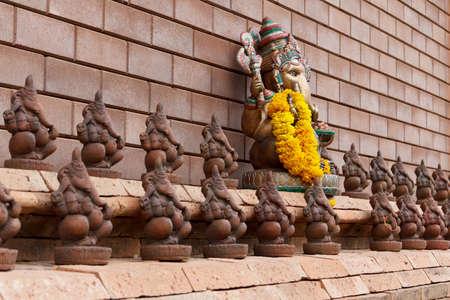 golden and small clay ganesha lined up along the brick wall photo