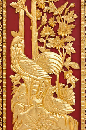 golden cock on red wood background photo