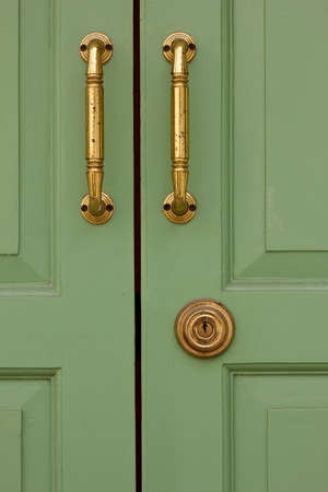 vintage green wooden doors with antique brass handles and keyhole Stock Photo
