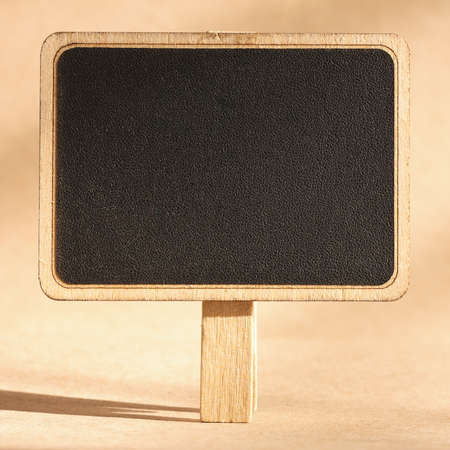 blank standing blackboard on brown background photo
