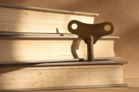winder: antique brass winder key standing on stack of old books for the key of success concept Stock Photo