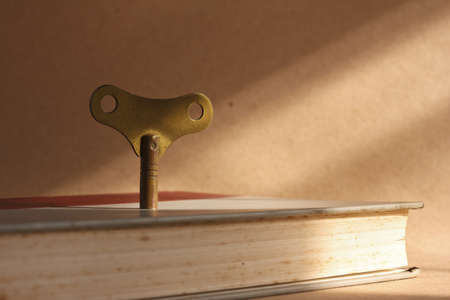 winder: antique brass winder key standing on old book for the key of success concept