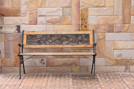 old vintage bench in front of sandstone wall Stock Photo