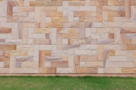 sandstone wall and green grass