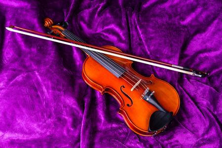 soumis: Photographie des objets. Instruments de musique. Violon avec archet sur un fond violet. Contexte - fourrure artificielle.
