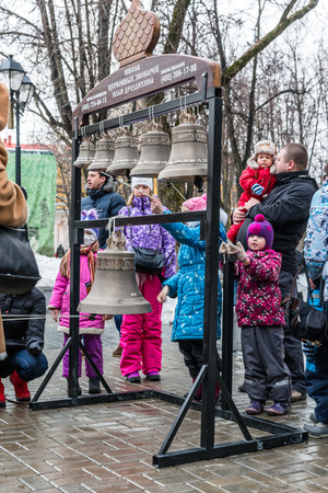 pancake week: WInter 2015. Day. Russia. Moscow. Maslenitsa (pancake week). Masterclass from the team of bell ringers Crimson Bells. The Children are trying to ring the bells.