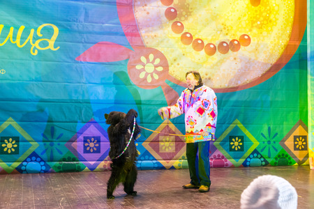 pancake week: Winter 2015. Day. Russia. Moscow. Maslenitsa (pancake week). The animal trainer with the bear on stage. Editorial