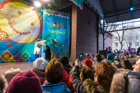 maslenitsa: Winter 2015. Day. Russia. Moscow. Maslenitsa (pancake week). People looking at the trainer with the bear wich performs on stage. Editorial