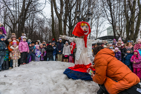 pancake week: Winter 2015. Day. Russia. Moscow. Maslenitsa (pancake week). Man sets fire to an effigy of Winter, around which there are people.