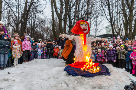 maslenitsa: Winter 2015. Day. Russia. Moscow. Maslenitsa (pancake week). Man sets fire to an effigy of Winter, around which there are people.