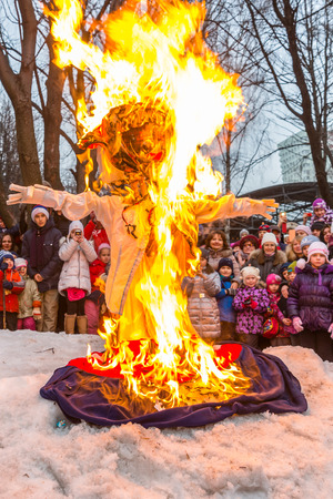 effigy: Winter 2015. Day. Russia. Moscow. Maslenitsa (pancake week). Burning the effigy of Winter, surrounded by people.