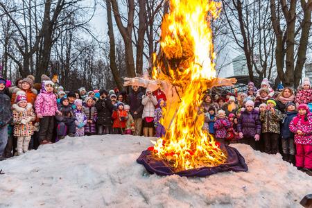 maslenitsa: Winter 2015. Day. Russia. Moscow. Maslenitsa (pancake week). Burning the effigy of Winter, surrounded by people.