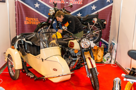 enfield: Winter 2015. Morning. Russia. Moscow. Crocus-Expo. Exhibition Motopark-2015 (BikePark-2015). Preparation for the exhibition. Man is wiping motorcycle (bike) with a stroller Royal Enfield. Editorial