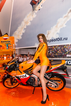 mopeds: Winter 2015. Morning. Russia. Moscow. Crocus-Expo. Exhibition Motopark-2015 (BikePark-2015). Beautiful girl on sports bike near the stand with oils.