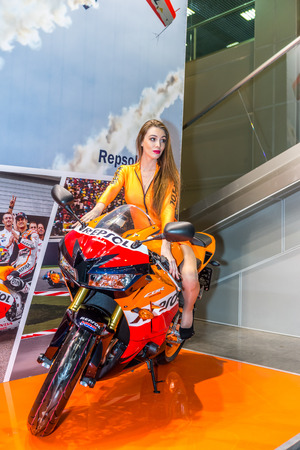 Winter 2015. Morning. Russia. Moscow. Crocus-Expo. Exhibition Motopark-2015 (BikePark-2015). Beautiful girl on sports bike near the stand with oils.