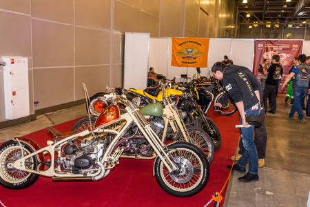 instance: Winter 2015. Morning. Russia. Moscow. Crocus-Expo. Exhibition Motopark-2015 (BikePark-2015). Custom Zone. Visitors are watching on the unique motorcycles.