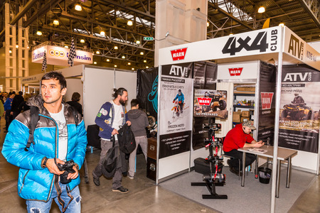 4x4: Winter 2015. Morning. Russia. Moscow. Crocus-Expo. Exhibition Motopark-2015 (BikePark-2015). The visitors are looking at stands. Stand of th ATV 4x4 Club.